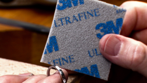 Abrasive sponge being used on a platinum ring band