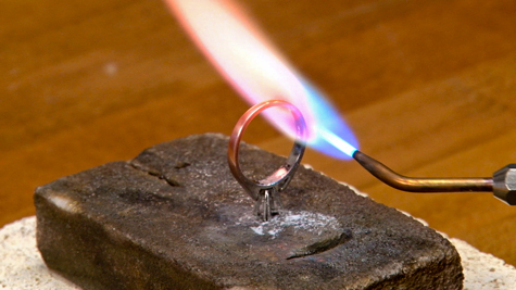 Alumina soldering block being used to solder a platinum solitaire ring