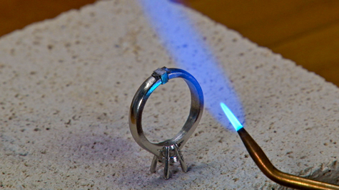 Torch with single cone tip being used to solder a platinum ring setting
