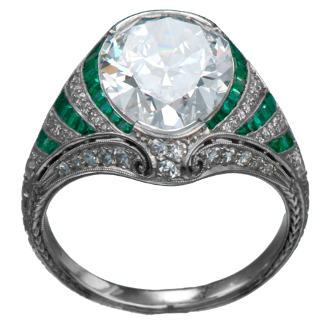 Perspective view of platinum ring with large diamond as the center stone. The shank is elaborate, with emerald baguettes alternating with channel-set round diamonds, millgrain, and other fine details.