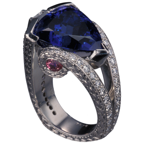 Perspective view of platinum ring with a large, trillion-cut tanzanite protected by a partial bezel as the center stone. The split shank is detailed with small gemstones, fine engraving, and millgrain.