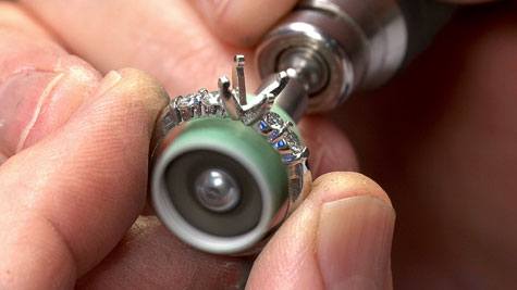 Close-up view of a jeweler using a rotary burnisher to prefinish the inside of a platinum ring