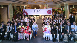 A large group of people sit for a photo to mark the opening of the Macau chapter. A GIA banner hangs behind them.
