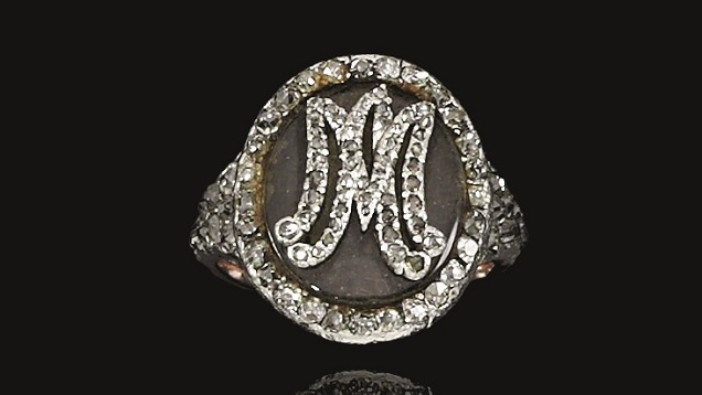 A small oval shape ring holds a lock of Marie Antoinette's hair. Her initials are set in small rose cut diamonds on the top of the oval.