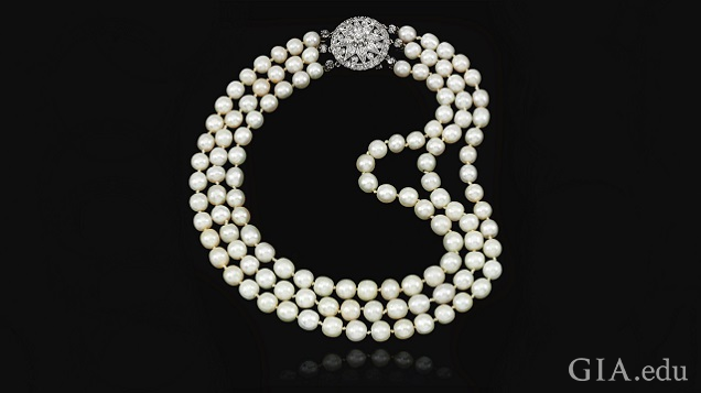 Three strands of pearls with a diamond clasp.