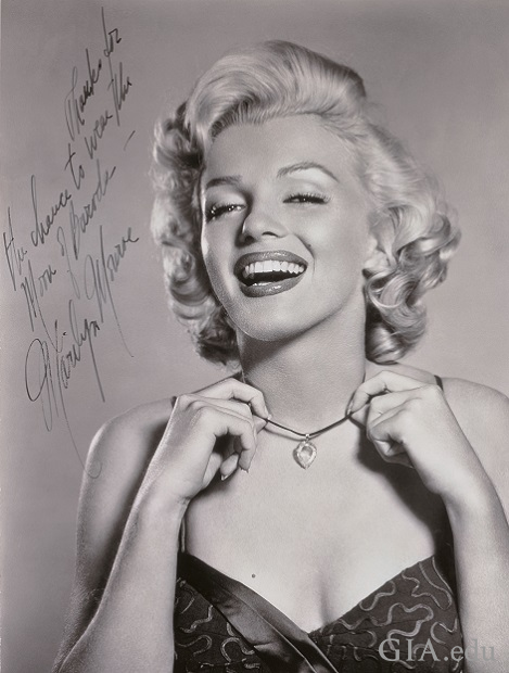 "A black and white photo of a smiling Marilyn Monroe wearing the Moon of Baroda. It is signed: ""Thanks for the chance to wear the Moon of Baroda – Marilyn Monroe""."