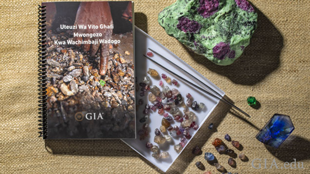 GIA's artisanal mining guide accompanied by gemstones, tweezers, a loupe and tweezers