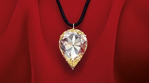 A large pear shaped yellow diamond hangs from a black cord and lies against red material.