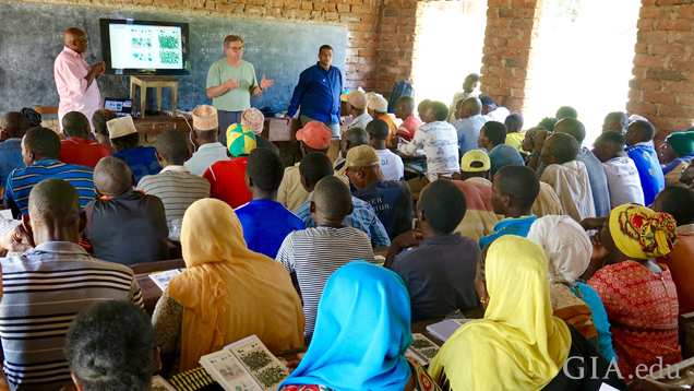 Pact representative Norbert Massay, GIA Graduate Gemologist (GG) Marvin Wambua and GIA's library director Robert Weldon explaining the gem guide to artisanal miners in MoroGoro, Tanzania. Photo by Pedro Padua/GIA.