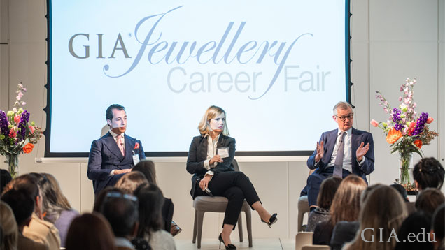 """Three panelist sit in front of the """"GIA Jewellery Career Fair"""" logo speaking to the audience."""