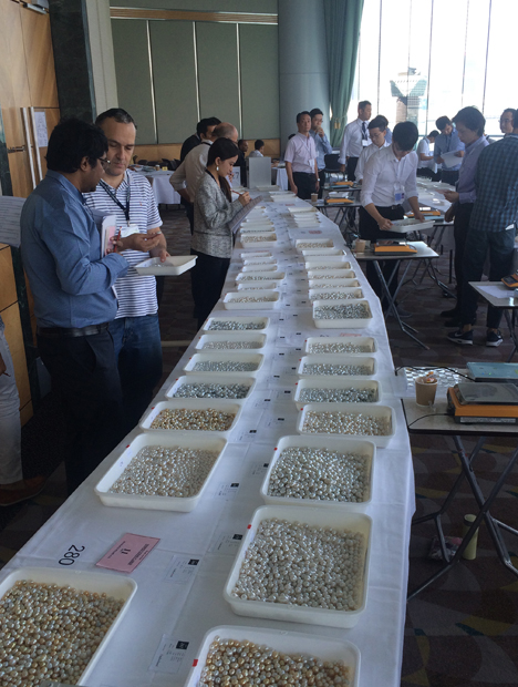 Buyers inspect lot of pearls spread out on long tables.