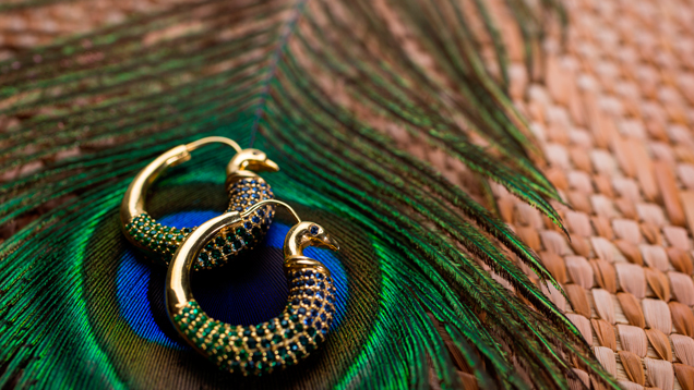 Hoop earrings with blue and green gems that mimic the colours of a peacock's tail.