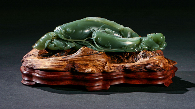 Green nephrite carving on a carved wooden base