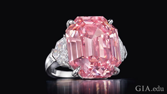 The large pink centre stone of this ring is a cut-cornered rectangular-cut diamond. It is flanked by colourless diamonds.