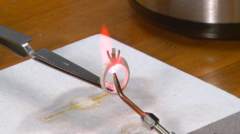 Photograph of a platinum peg setting being soldered to a yellow gold mounting using a torch