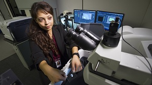 Young woman works with a Raman spectroscopy machine.