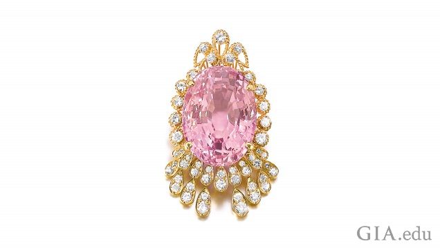 An oval pink sapphire framed by diamonds.