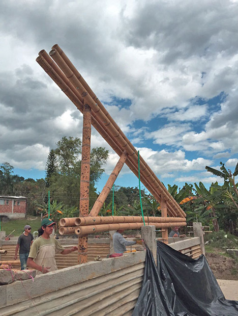 """Ringsrud's Clayhands, which has six employees, provides homes for the many displaced people in Colombia's rural areas by training young, local men in earth-friendly, alternative forms of construction. Workers construct a concrete support for an adobe wall and guadua (""""large bamboo"""") roof supports for a building in Sasaima, Colombia, two hours north of Bogotá. Photo by Ron Ringsrud"""