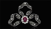 ダイヤモンドでできた3つのリボンが蝶結びを作り、中心にあるルビーの周りを多くのダイヤモンドが囲む。