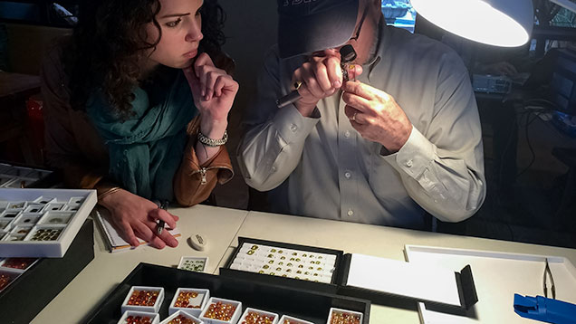 JTV staff looks at a dealer's gemstones