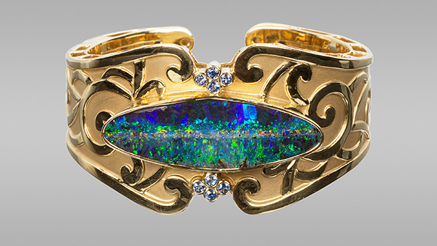 Boulder opal and sapphires in cuff bracelet.