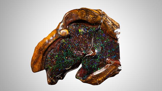 Broken boulder opal with light pattern of color.