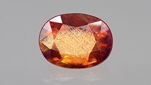 Transparent oval-cut orange sapphire with golden sheen.