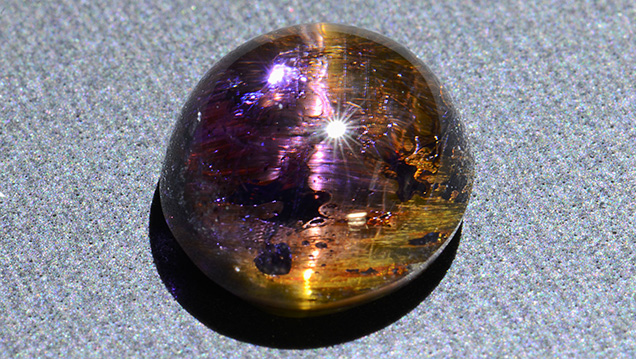 This cabochon displays an unusual yellowish chatoyancy.