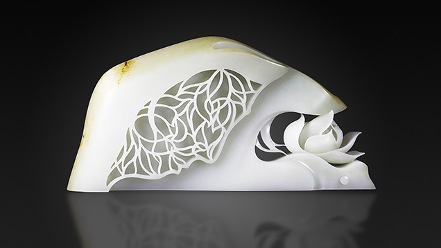 White nephrite Buddhist carving featuring openwork papercut-style and a carved lotus.
