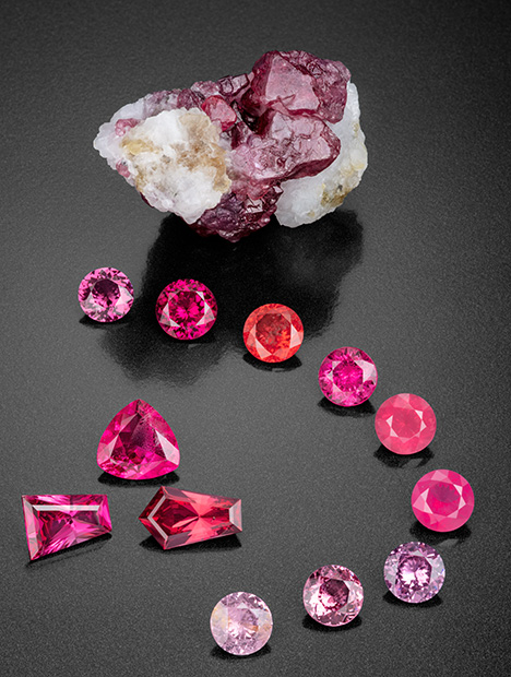 Figure 2. This remarkable suite of spinel gems faceted by Bill Vance shows a wonderful range of color and transparency. The 232.9 ct rough mineral specimen gives clues to the crystal's origin, with remnants of the marble host rock preserved. The faceted