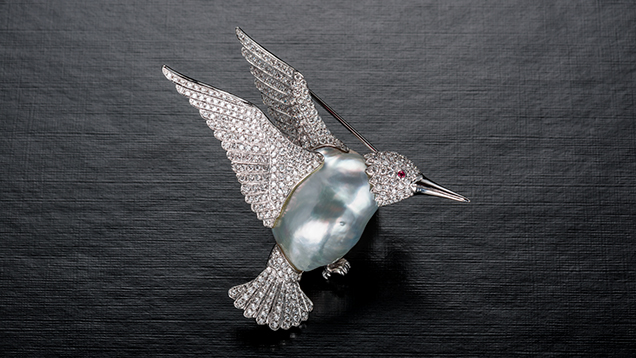 Hummingbird brooch with a baroque pearl surrounded by diamonds.
