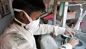 Gem cutters in Jaipur wear masks provided by AGTA.