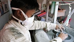 Gem cutters in Jaipur wear masks provided by AGTA.