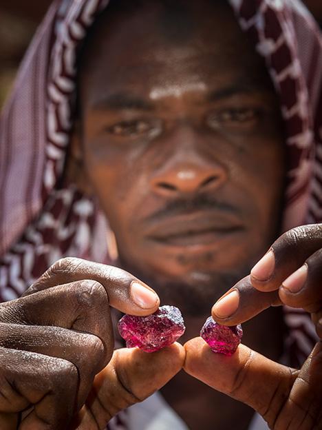 A miner in northern Tanzania examines rhodolite.