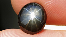 A black star sapphire with one set of golden rays and another set of silver rays.