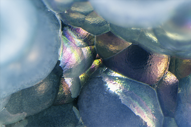 Iridescent thin-film interference colors seen on a thin layer of chalcedony.