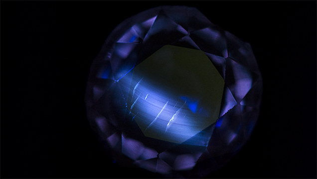 Flame-fusion synthetic sapphire displays curved banding under short-wave UV light.