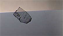 Surface-breaking crystal seen in red spinel.