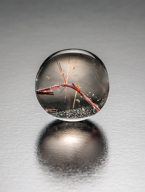 Bent rutile visible within the polished rock crystal quartz.