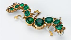 このサンショウウオの形をしたエナメルゴールドの帽子飾りは、チープサイドの財宝の最も象徴的な品物の一つである。 前面のエナメルは、歯に似せた小さな黒い斑点のある開いた口を表している。 ピンはコロンビア産のカボション・エメラルドで飾られ、尾はテーブルカット・ダイヤモンドがセットされている。