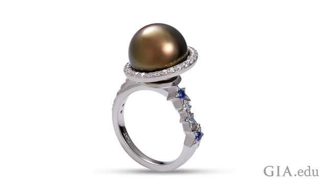 A black Tahitian pearl is encircled by a ring of diamonds. Four stars, with sapphires and aquamarines in their centers, cascade down one side of the shank.