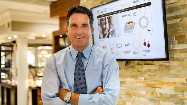 Sean Dunn(肖恩·邓恩)站在一个屏幕前,屏幕上显示着他的店铺网站。