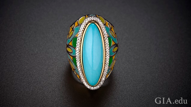 An elongated oval piece of turquoise is framed by diamonds with a enameled shank of turquoise, green, yellow and orange colors.