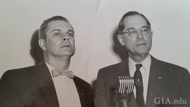 Two men in front of a microphone.