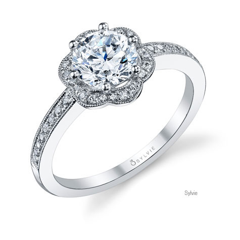 Perspective view of platinum ring designed by Sylvie, featuring a flower-shaped diamond halo surrounding a large center diamond, and diamonds set halfway down the shank.