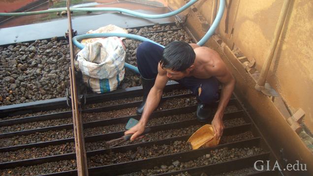矿工蹲在装满蓝宝石的托盘上方清洗和挑拣。