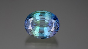 An oval shaped bicolor tanzanite has purple on each side with blue-green in the middle.