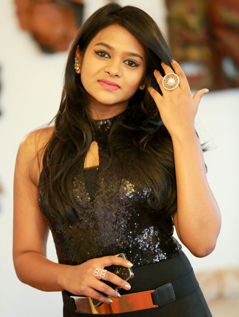Trishala Ashok, in a black outfit, wears one of her spaceship-inspired rings.