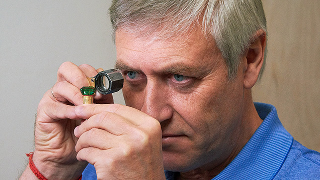 Tuzlukov examines the square cushion-cut tsavorite.