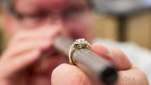 一个人拿着一根长长的金属圆形柱,上面有一枚戒指。 焦点集中在戒指上,而不是他在背景中的脸。